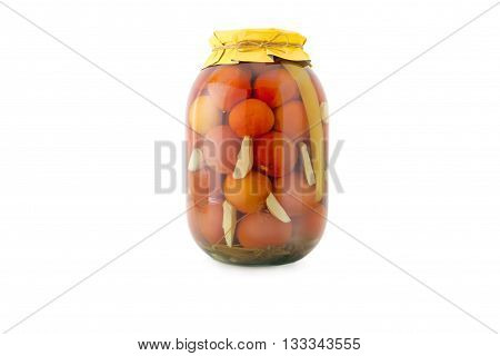 Homemade pickled tomatoes in glass jar with yellow paper wrapper. Homemade preserves, pickles. Jar of canned marinated tomatoes isolated on white