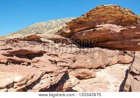 Pot Alley gorge landscape with red sandstone rugged terrain and native plants under clear blue skies in Kalbarri, Western Australia.