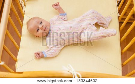 lying two month old baby girl in cot