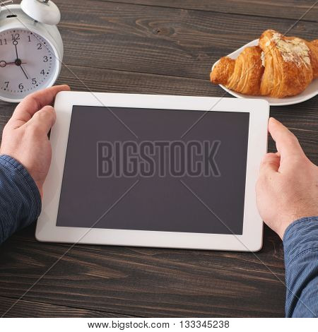 Man communicates over the Internet with help of a tablet computer in the morning. man holding tablet computer with a blank screen where you can post your test closeup sitting at a dark wooden table