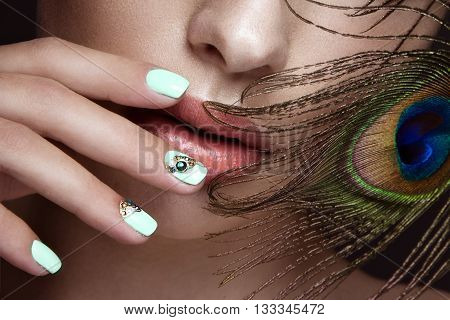 Beautiful girl with manicure design and peacock feather on her face. Art nails. Photos shot in the studio.