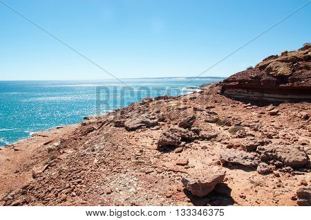 Red sandstone cliffs overlooking the turquoise Indian Ocean seascape at Pot Alley in Kalbarri, Western Australia under clear blue skies.