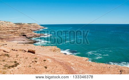 Layers of sandstone bordering the Indian Ocean coastline from elevated overlook at Pot Alley in Kalbarri, Western Australia under clear blue skies.