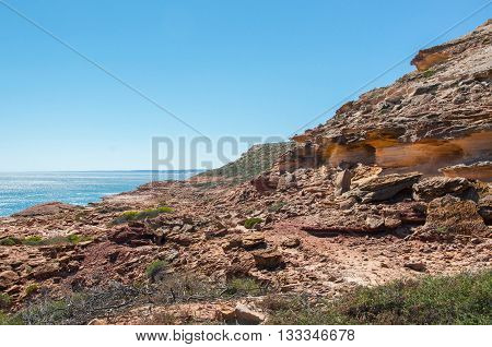 Rocky Indian Ocean coastline with red sandstone cliffs at Pot Alley in Kalbarri, Western Australia with glistening ocean waters under clear blue skies.