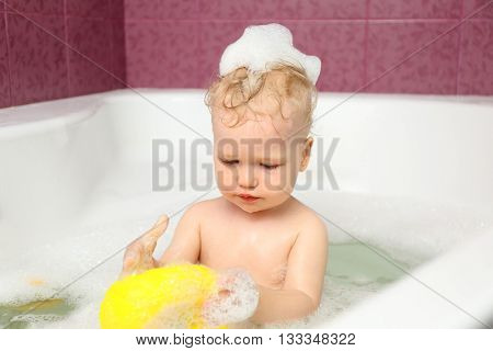 Cute baby boy playing with toys in bath