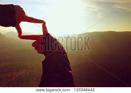 Close Up Hands Making Frame Gesture. Orange Misty Valley Bellow. Sunny Spring Daybreak In Mountains.