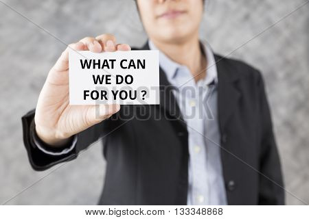 Businessman Presenting Business Card With Word What Can We Do For You