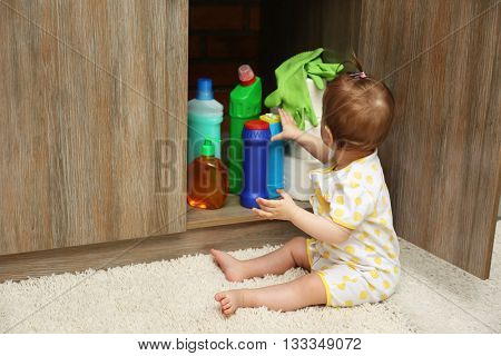 Little girl playing with detergents in kitchen