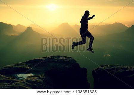 Crazy Hiker Jump Between Cliffs. Amazing Mountains, Heavy Mist