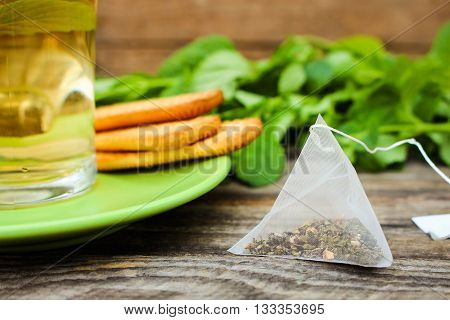 Tea bag on background of mint, cookie and cup of tea