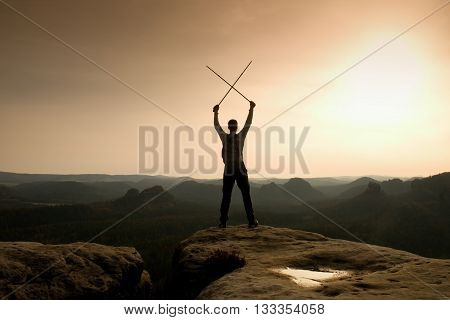 Happy Backpacker With X Crossed Poles In The Air, Open Misty Mountain Valley Bellow Cliff. Silhouett