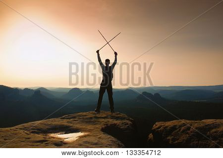 Man With Crossed Poles Above Head On Cliff.  Foggy  Mountain Valley Bellow.  Sunny Spring Daybreak I