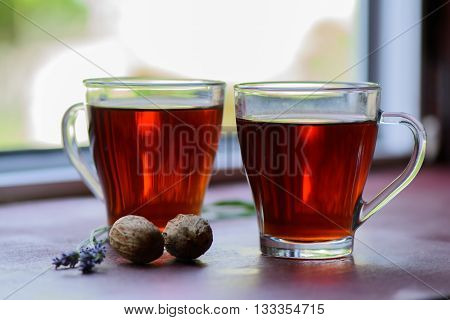 Two cups of tea on the window sill and nuts