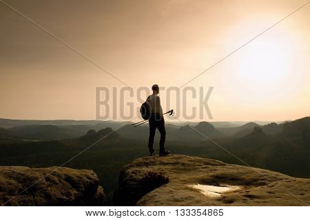 Tall Ginger Hair Hiker In Grey T-shirt And Dark Trekking Trousers On Cliff. Man With Tourist Poles I