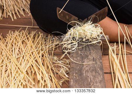 Female hand manually whittling bamboo for making wicker art