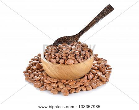 uncooked pinto beans in wooden bowl on white background
