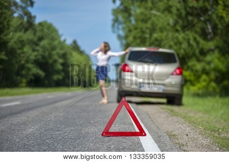 Young woman calling for car assistance after breakdown on the road.Closeup of Red triangle warning sign on the road. Focus on triangle.