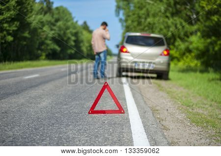 Red triangle warning sign on the roadside. Man after breakdown calling to a car assistance