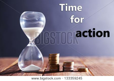 Hourglass with coins on wooden table on gray background