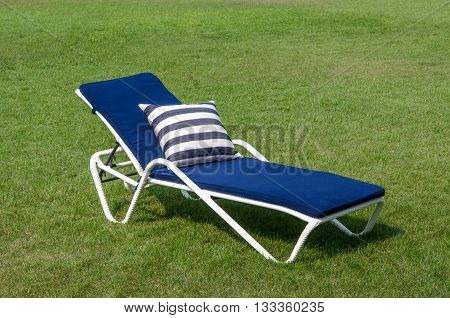 White rattan sun lounger and pillow in the garden