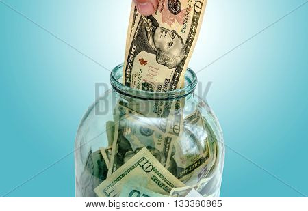 money is invested in a glass jar on a blue background