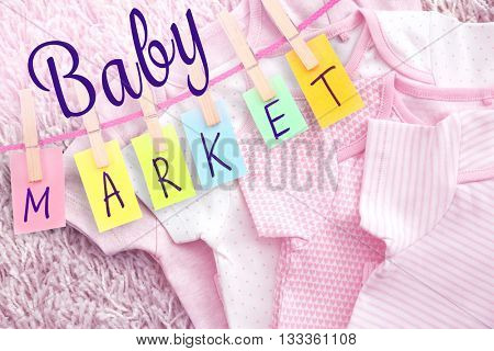 Children clothes and colorful word hang on rope by wooden peg. Baby market concept