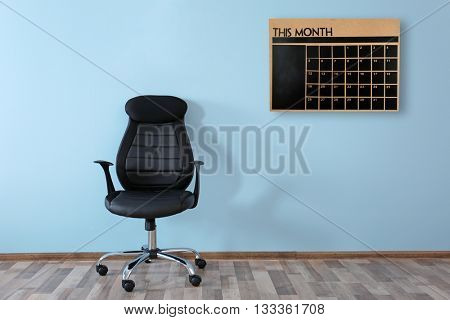 New office chair and chalkboard calendar on wall background