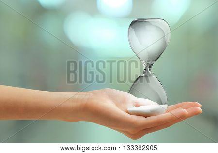 Hourglass in female hand on blurred background