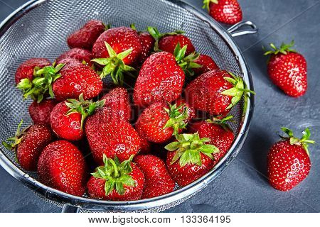 Close up of many fresh and juice strawberries in sieve