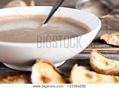 Close up of creamy vegan mushroom soup with champignon and shiitake in white bowl. Wood background. Dry shiitake on front.
