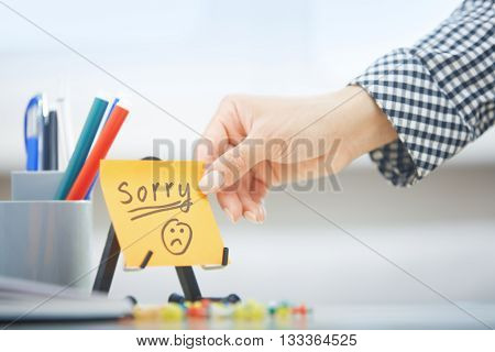 Human hand holding adhesive note with Sorry text