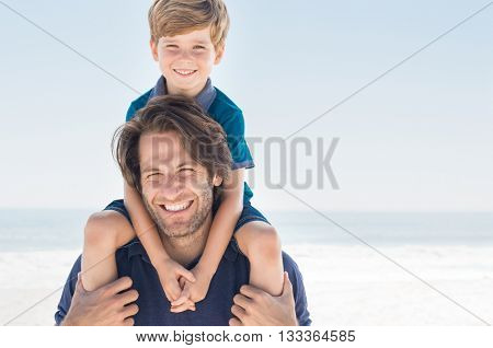 Father holding son on shoulder. Portrait of happy father and son smiling and looking at camera. Father giving his son piggyback at beach.