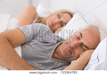 Senior man and woman sleeping. Senior man and woman resting with eyes closed. Mature couple sleeping