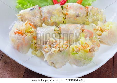 Spring rolls on white plate wooden background