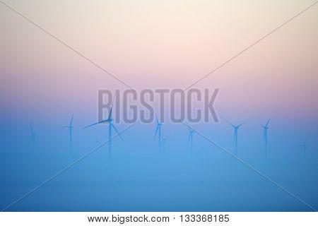 wind turbines on field on foggy morning