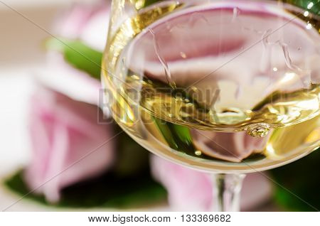 Close up of white wine in wineglass and roses background