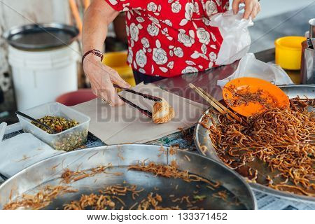 Woman packing curry puff to the plastic bag at Kimberly Street Food Night Market