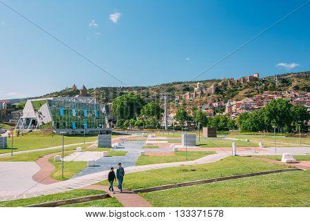 Tbilisi, Georgia - May 19, 2016: Young people walking in the park Rike in Tbilisi, Georgia. In the background is visible cableway, Narikala fortress.
