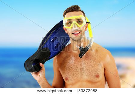 Young man with swimming mask or goggles with flippers on blurred sea background