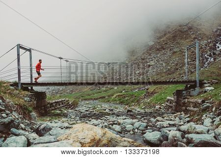 Man trail running on a path in the mountains