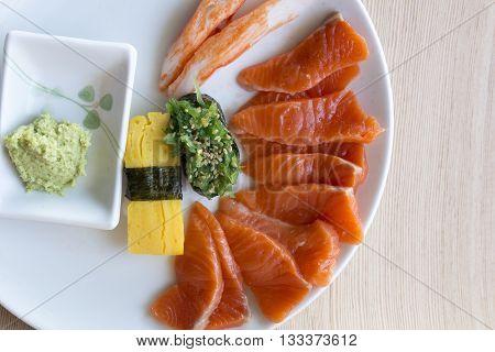 Salmon sashimi and wasabi set in white disc
