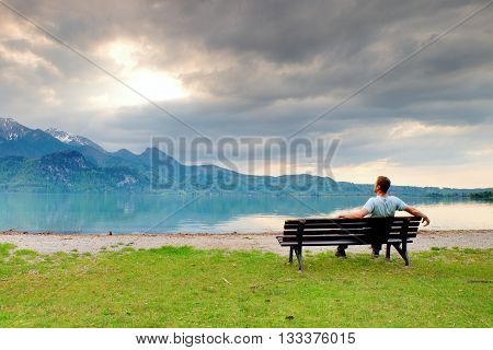 Alone  Man Sits On Bench Beside An Azure Mountain Lake. Man Relax