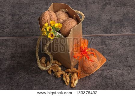 Walnuts in a paper bag and a small bouquet of wild flowers on a dark background a little surprise