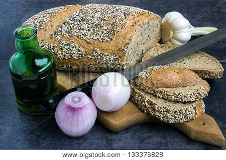 Whole wheat bread and rye sprinkled with sunflower seeds sesame seeds and poppy seeds sliced on the board next to the olive oil and onions