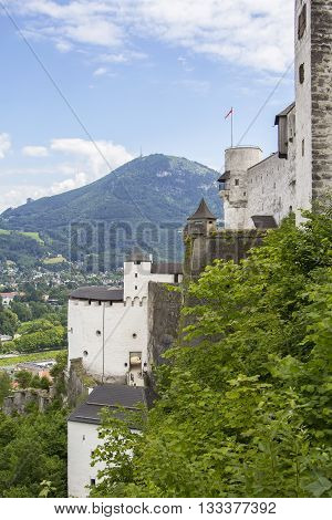 Background landscape view of the walls of Hohensalzburg Fortress and the surrounding hills and mountains in Salzburg, Austria