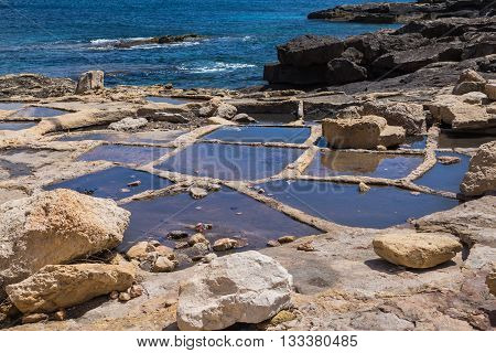 Holes in rocks at the seaside of the Mediterranean sea for evaporation the water and getting sea salt. City Marsaskala island Malta.