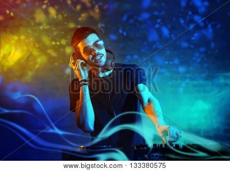 DJ playing music at mixer on foggy background