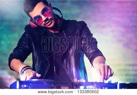 DJ playing music at mixer on blurred brick wall background