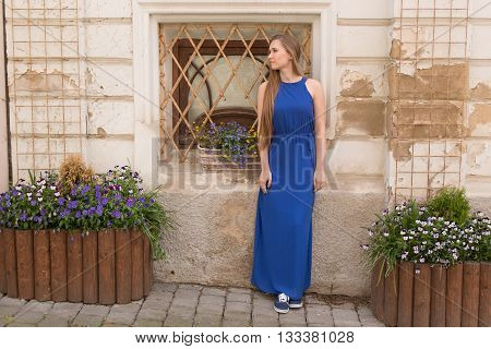 Modest young girl on the background of the old wall with windows