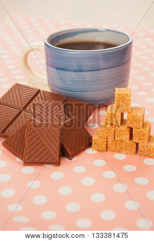 Blue Cup Of Tea  Lump Sugar And Chocolate On Pink Background